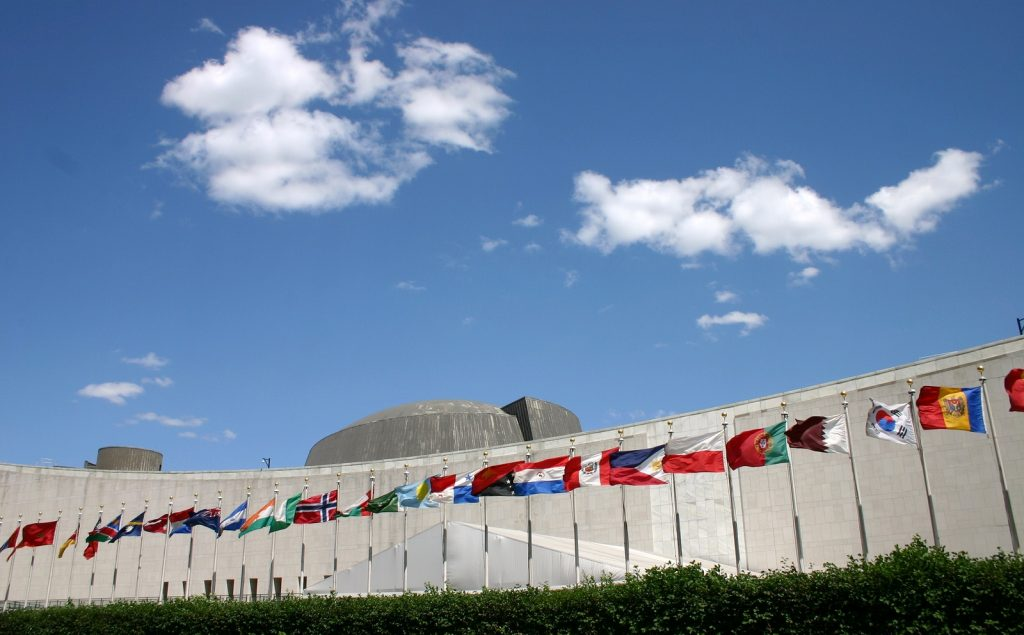 United Nations headquarters building in New York USA with the Flags of Nations in front.
