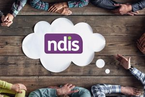 A birds-eye view of the NDIS logo on a paper speech bubble sitting on a wooden desk. Six people sit around the desk. Only their arms are visible.