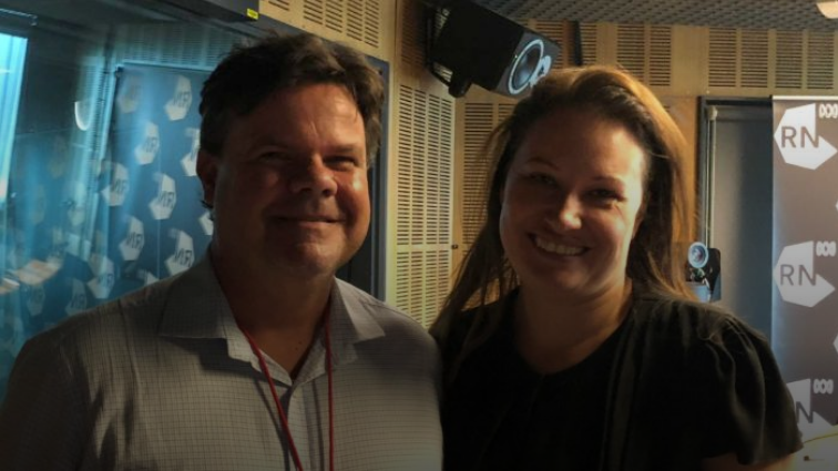Two people, Damien Griffis and Larissa Behrendt, stand next to each other in a radio studio and smile at the camera