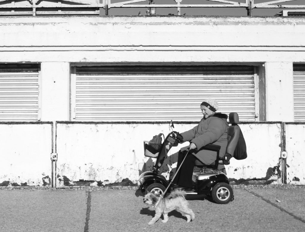 woman wearing a large coat driving past an old building on a mobility scooter. Her dog walks along beside the scooter on a leash.