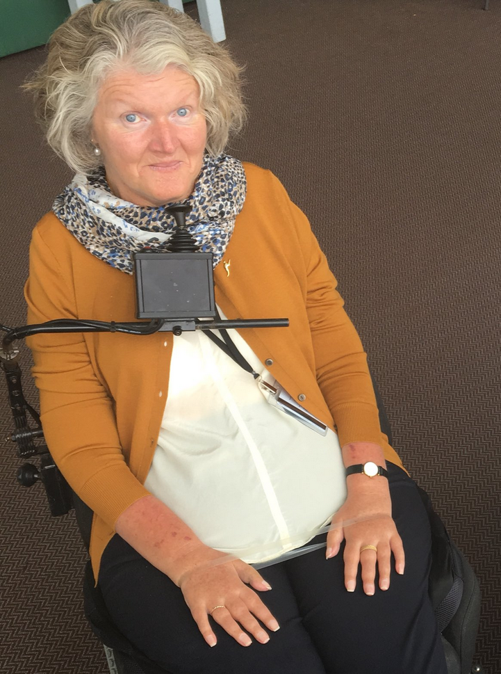A woman, Rosemary Kayess, sits a wheelchair with her hands on her lap. She has blonde grey hair and wears a mustard coloured cardigan over a white shirt and scarf. A controller is positioned beneath her chin. Credit: Unknown