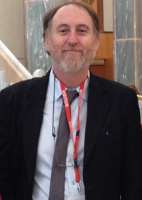 A man with a short grey beard smiles toward the camera. He is wearing a dark suit, light shirt, and a grey tie.