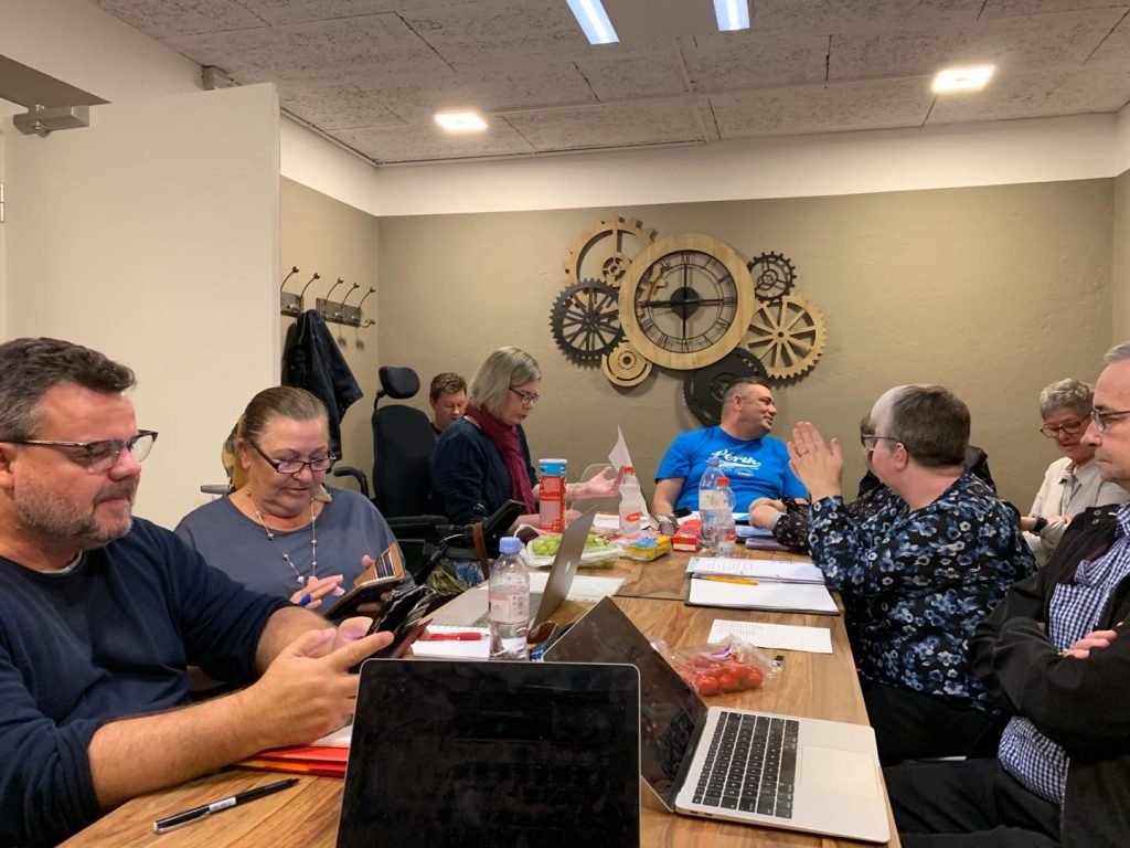 A group of people with disability sitting casually around a table covered in laptops, notebooks and water bottles. They are in a small room with a clockwork sculpture on the wall.
