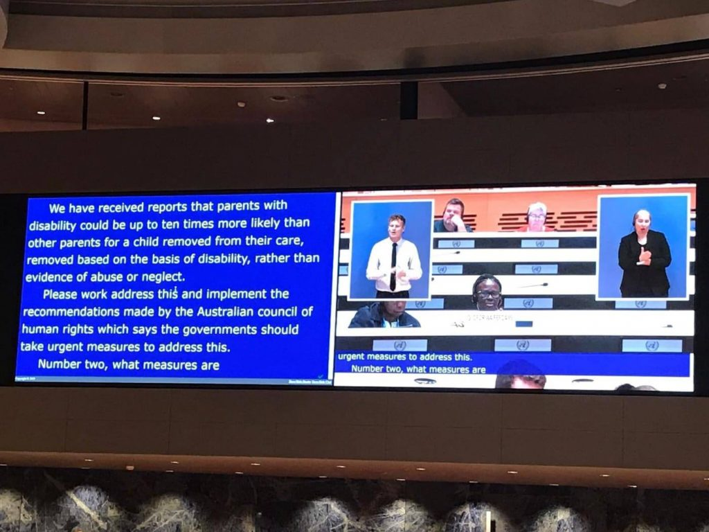Photo of the projection screen from the UN session, showing interpreters and text captions.