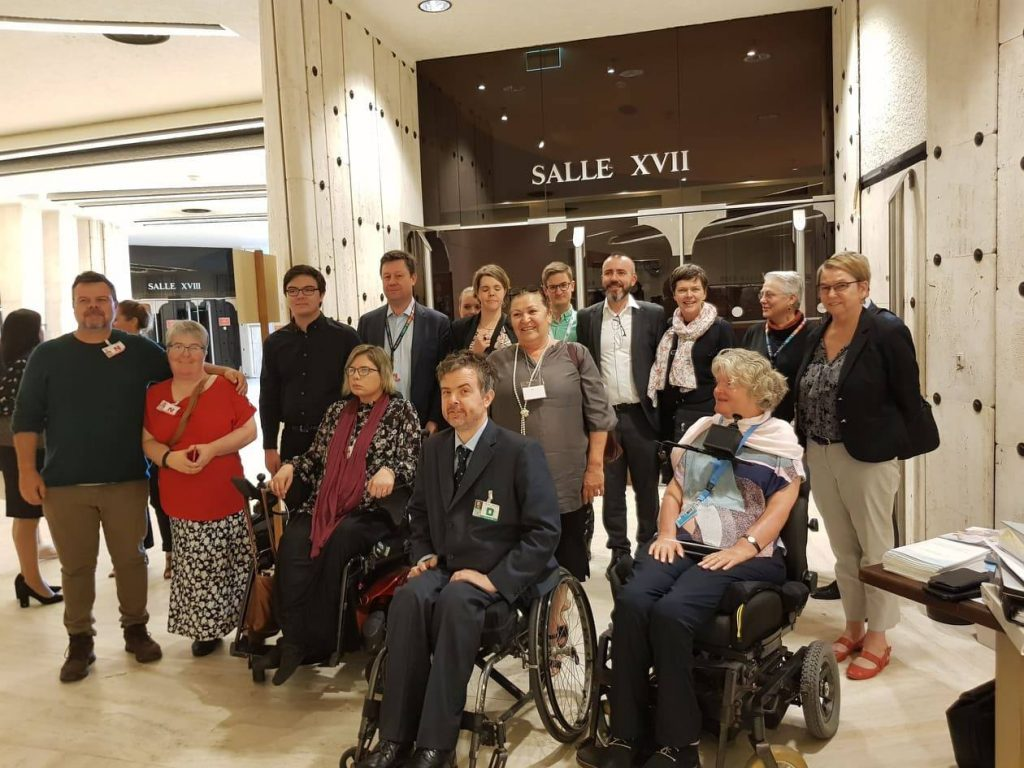 A group of people standing or sitting in wheelchairs, including the Australian civil society delegation and Ben Gauntlett.